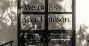 "Black and white photo of storefront windows with the text ""We Miss you Tucson"""